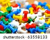 Group of colorful push pins on cork bulletin board - stock photo