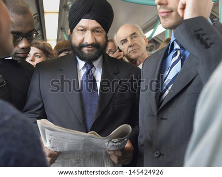 Group of commuters reading newspaper and using cellphone in train - stock photo