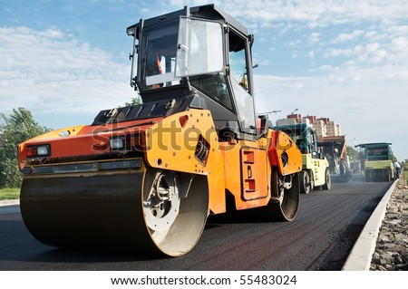 Group of compactors and Heavy Vibration rollers at asphalt pavement works (road repairing) - stock photo
