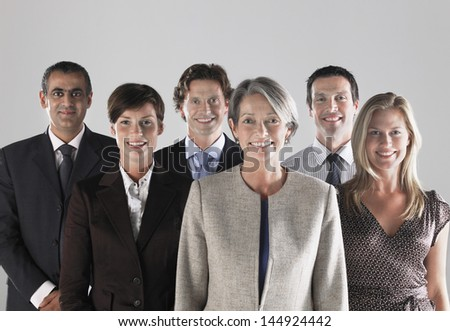 Group of confidence businesspeople smiling against gray background - stock photo