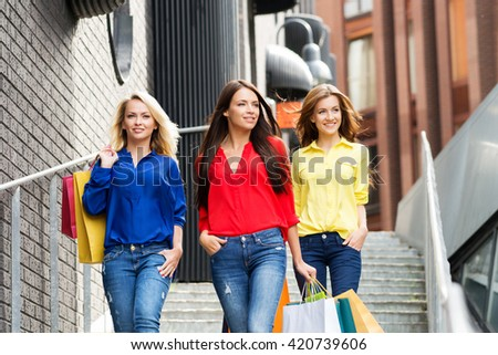 Group of confident beautiful girls going down the outside stairs with shopping bags.