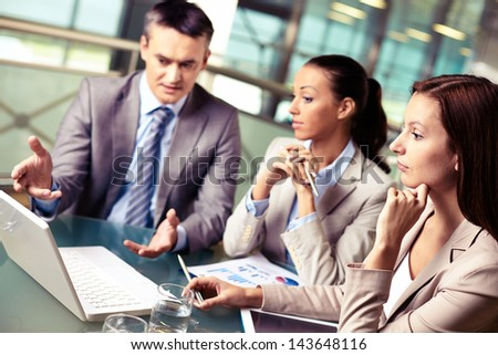 Group of confident business partners looking at laptop display at meeting, focus on pensive woman