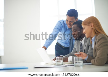 Group of confident business partners working with laptop in office - stock photo