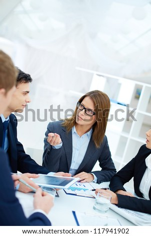 Group of confident businesswoman listening to her partner while looking at him at meeting - stock photo