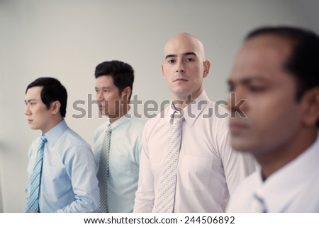 Group of confident serious businessmen, selective focus - stock photo