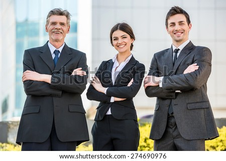 Group of confident successful smiling businesspeople in suits at a meeting. - stock photo