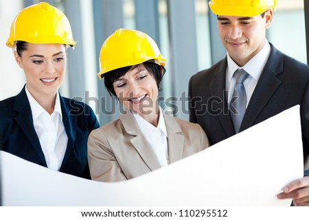 group of construction managers discussing project on blue print - stock photo