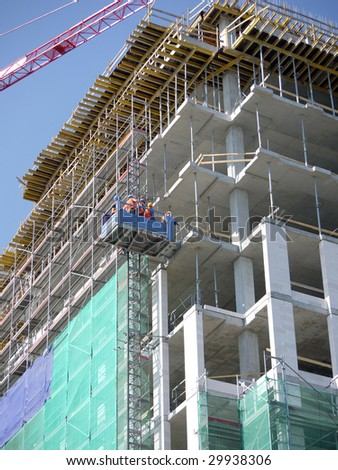 Group of construction workers going up the multistorey building using external lift to start their day shift - stock photo