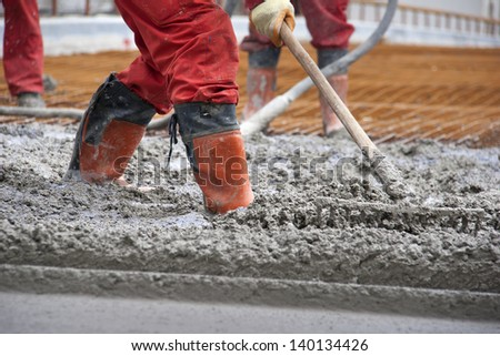 Group of construction workers spreading freshly poured concrete mix on the bridge - stock photo