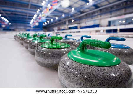 Group of curling rocks on ice - stock photo