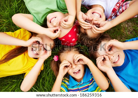 Group of cute children lying on grass  - stock photo