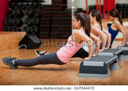 Group of cute female Hispanic friends exercising together during a gym class - stock photo