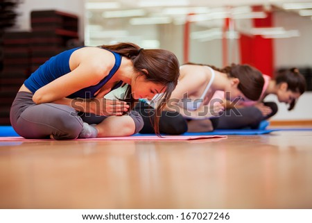 Group of cute Hispanic women relaxing and meditating during their yoga class in a gym - stock photo