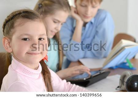 group of cute kids doing homework together at the table at home - stock photo