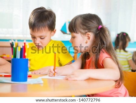 Group of cute little preschol kids drawing with colorful pencils - stock photo