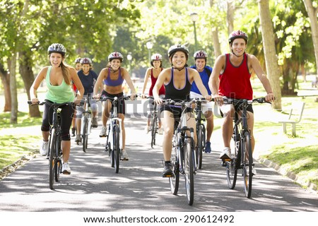 Group Of Cyclists On Cycle Ride Through Park - stock photo