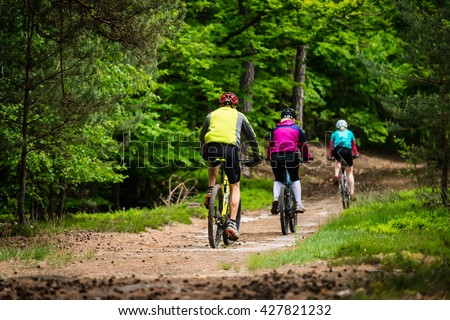 Group of cyclists on the forest trail. Family trip on bikes in lush green. - stock photo