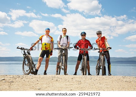 group of cyclists on the shore of a mountain lake. team outdoors. mountain bike - stock photo