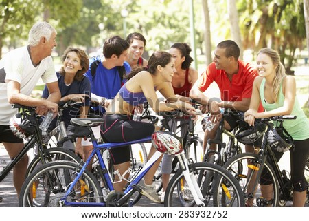 Group Of Cyclists Resting During Cycle Ride Through Park - stock photo