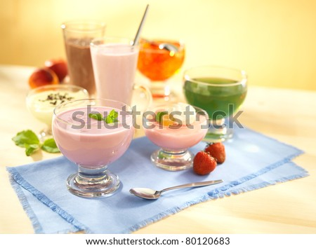 Group of dairy and fruit desserts with pudding, fruit jelly, shake and joghurt on table with spoon - stock photo
