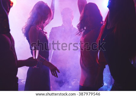 Group of dancing people in night club - stock photo