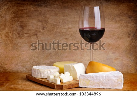 group of different cheese with glass of red wine on a vintage wooden background - stock photo