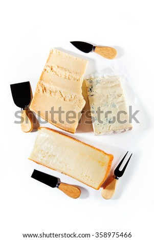 Group of different pieces of cheese and knives for cutting cheese. Parmesan, Gorgonzola, Cheddar - stock photo
