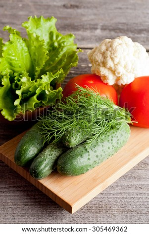 Group of different vegetables on wooden plank, close up, vertical - stock photo