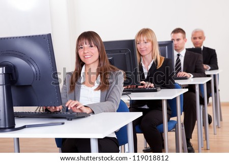 Group of diverse business people working in a support centre sitting at desks in front of computer monitors responding to email enquires - stock photo