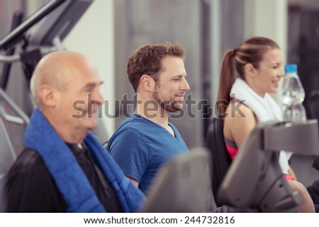 Group of diverse people in a gym working out together on the equipment with an elderly man and young woman with focus to the smiling face of a young man in the centre, in a health and fitness concept - stock photo