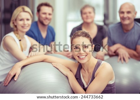 Group of diverse people in a pilates class at a gym posing with their gym balls looking at the camera with focus to an attractive young woman in the foreground