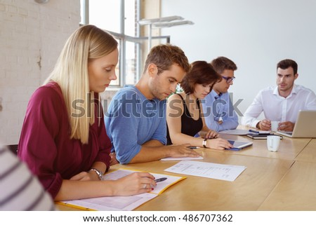 Group of diverse young businesspeople in a meeting in a boardroom sitting at the conference table working on paperwork
