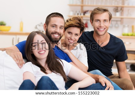 Group of diverse young friends relaxing at home grouped together on a sofa and smiling happily at the camera - stock photo