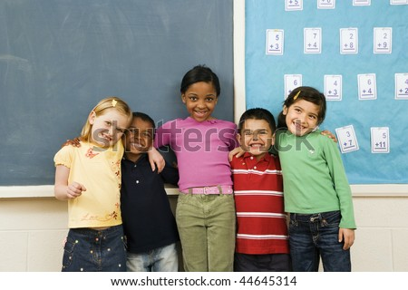 Group of diverse young students standing together in classroom. Horizontally framed shot. - stock photo