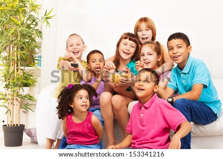 Group of diversity looking kids, boys and girls sitting on the coach, laugh, change channels on TV and eat popcorn while watching movie - stock photo