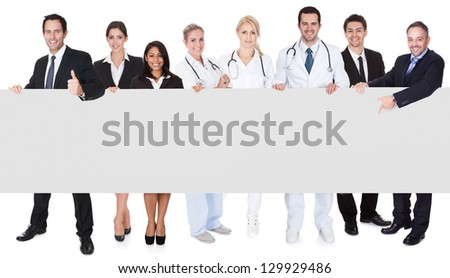 Group of doctors and managers presenting empty banner. Isolated on white - stock photo