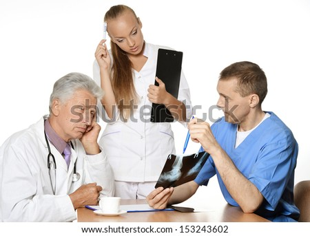 Group of doctors discussing x-ray at table - stock photo