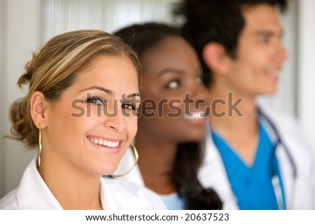 group of doctors in a hospital smiling - woman leading