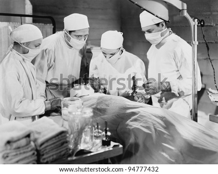 Group of doctors performing surgery - stock photo
