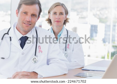 Group of doctors posing at their desk wearing breast cancer awareness ribbon - stock photo
