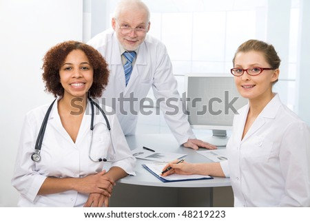 Group of doctors sit on a workplace and look at the camera - stock photo