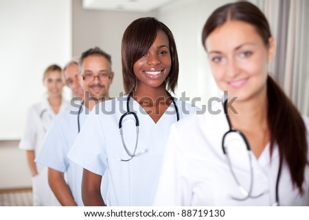 Group of doctors standing at a hospital in a row - Smiling at the camera - stock photo