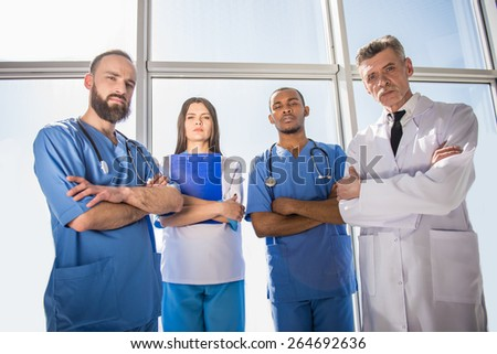 Group of doctors standing with arms crossed in  hospital. - stock photo