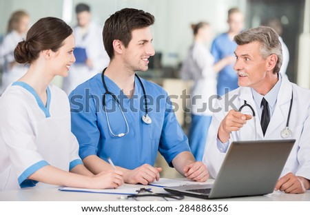 Group of doctors working together on a laptop at doctor's office. - stock photo