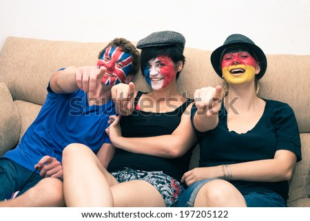 Group of ecstatic sports fans cheering at home and pointing at you. - stock photo