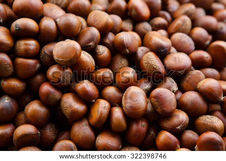Group of edible chestnuts. Dark background.  - stock photo