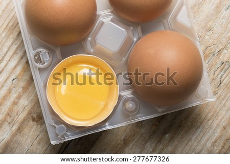 group of eggs with one opened with yolk  in plastic basket on wooden table - stock photo