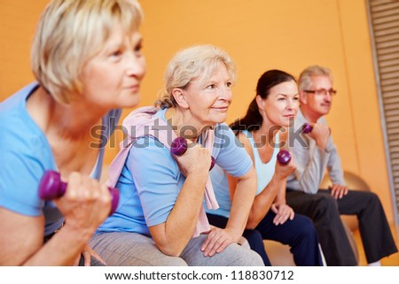 Group of elderly people doing senior sports in fitness center with dumbbells - stock photo