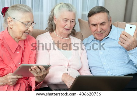 Group of elderly people. Group of older people having fun in communicating with the family on the internet in the comfortable living room  - stock photo