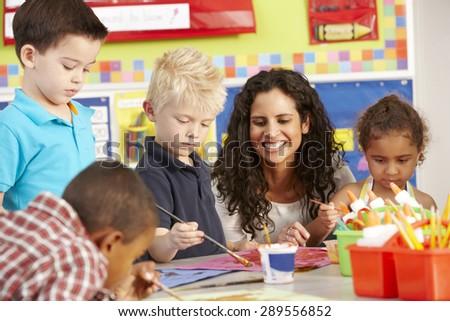 Group Of Elementary Age Schoolchildren In Art Class With Teacher - stock photo